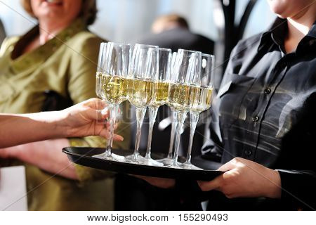 Waitress Holding A Dish Of Champagne And Wine Glasses