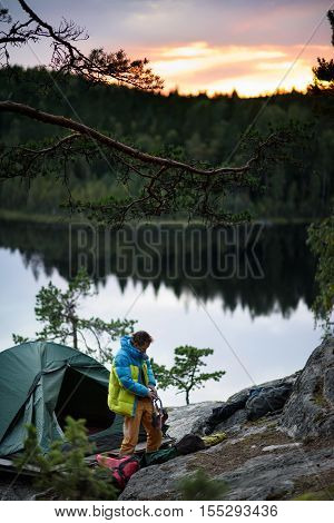 Young climber having a camp on a top of a cliff, a picturesque lake at sunset background.