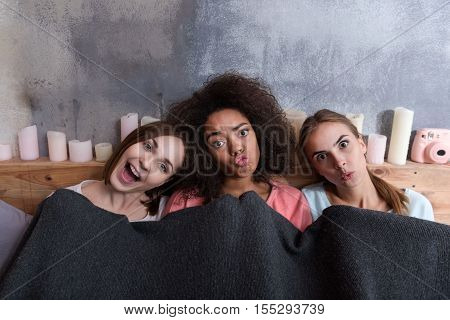 Acting ape with friends. Young cheerful amused girls acting ape and sitting close to each other while expressing happiness at home and being covered with the blanket