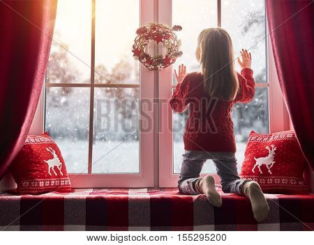 Merry Christmas and happy holidays! Cute little girl sitting by the window and looking at the winter forest. Room decorated on Christmas. Kid enjoys the snowfall.