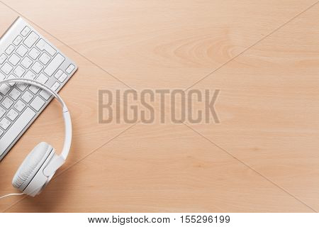 Headphones over pc keyboard on wooden desk table. Music concept. Top view with copy space