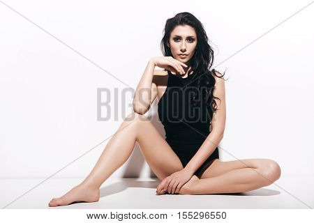Beautiful seductress. Attractive young woman in black swimsuit looking at camera while sitting in front of white background