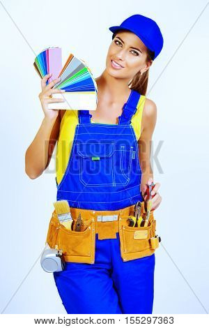 Smiling female consultant on building coatings shows samples palette of colors. Construction worker. Occupation.
