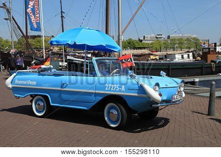 AMSTERDAM, NETHERLANDS - MAY 6, 2016: An amphibious (amphibian) vehicle is parked along the canal in Amsterdam, Netherlands.