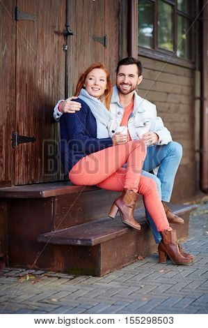 Happy young couple resting sitting on doorstep