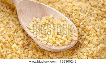 Raw bulgur in wooden spoon close up. Horizontal