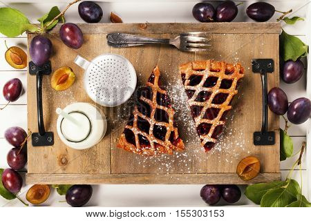 Plum tart, milk and fresh plums on rustic table