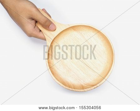 Hand holding empty wooden plate over white background. Top view