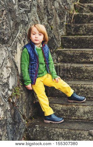 Outdoor fashion portrait of adorable little 4 year old boy, wearing blue waistcoat and boots, yellow trousers and green pullover
