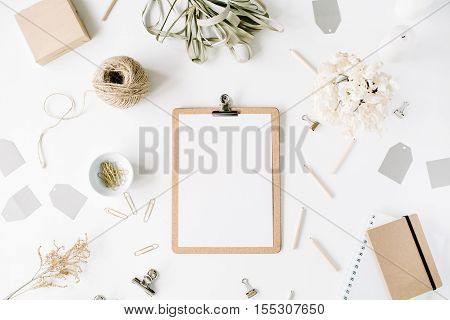 Flat lay top view office table desk. feminine desk workspace mock up with clipboard twine pencils floral bouquet craft diary and clips on white background.