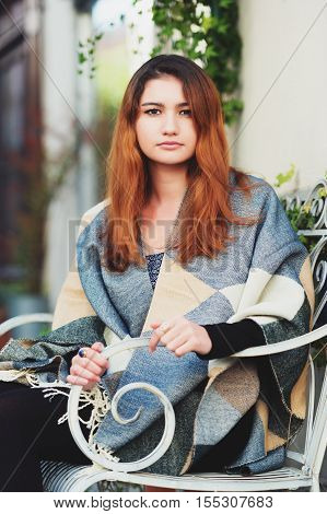 Young fashion 20 year old girl sitting on the bench, wearing warm plaid jacket