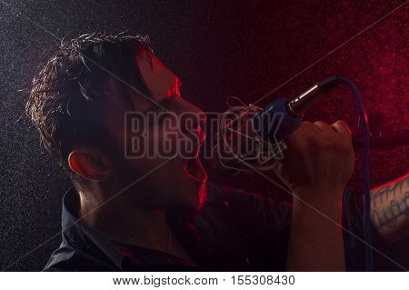Portrait of young expressive rock performer with microphone in his hands at the background of water drops and red spotlights.