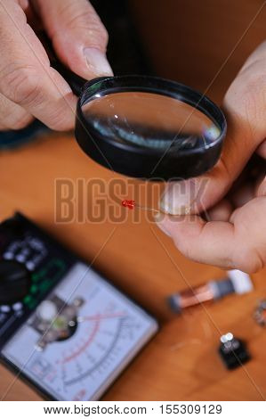 Male engineer checking diode with magnifier. Electrician equipment: multimeter chips and diodes.