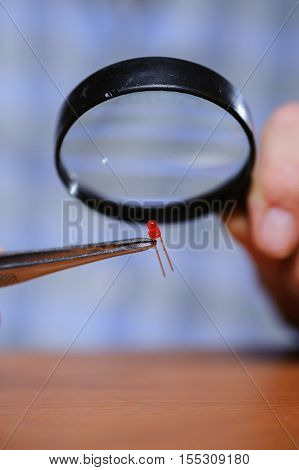 Closeup of diode and magnifier in male hands. Electronical components.