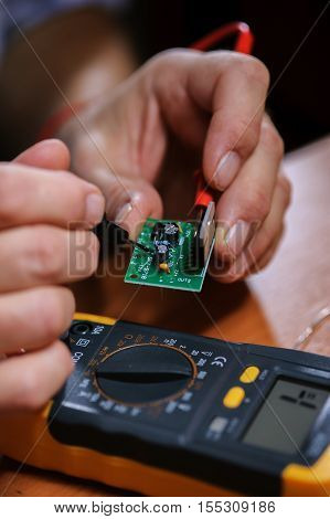 Closeup of male hands with multimeter and microcircuit. Electrician checking electronical components.