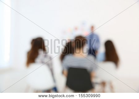Blurred background of business trainer giving presentation to group of people