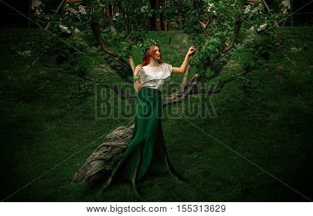 forest nymph with roots in a long skirt posing near a tree with a wreath on head. Horizontal portrait of beautiful girl in nature