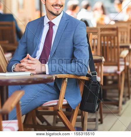 Closeup, handsome male has a french breakfast at sidewalk cafe outdoors. Smiling businessman. Elegant successful man. Has a mustache