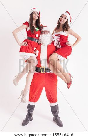 Strong Santa holding a hot girls at the hands. Santa girlfriend. Sexy babes. Christmas party 2016. Celebrating New Year 2017