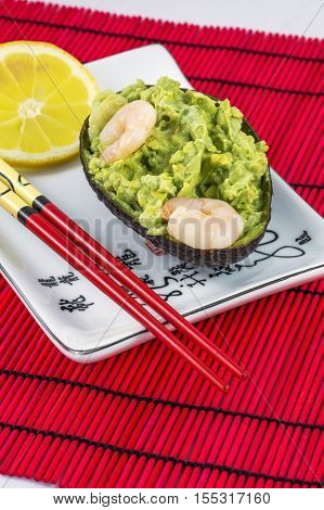 Avocado salad with shrimps, lemon and red chopsticks lies on the white plate