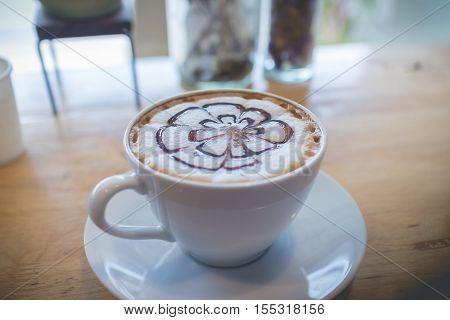 Hot coffee with foam milk art in afternoon break. Coffee cup. coffee mocha on the wood desk. Coffee break.(selective focus vintage effect)