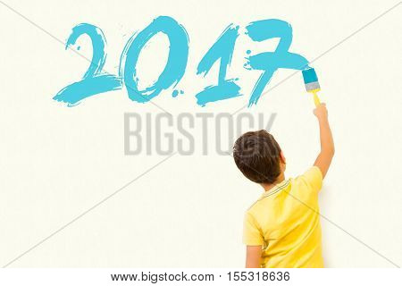 Cute little kid drawing new year 2017 with painting brush on wall background
