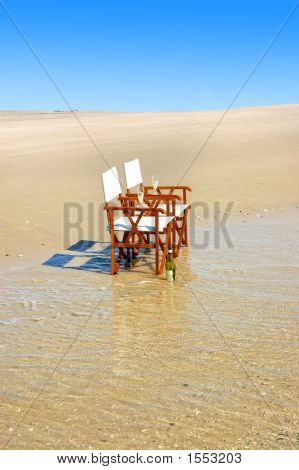 Deck Chairs At Waters Edge On The Beach