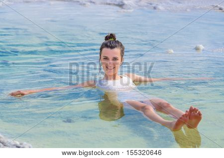 Sexy attractive girl wears white dress swims in water and looks to camera. Her hands and legs lowered into emerald sea. Young woman relaxing sitting on the edge of Baskunchak salt lake on white crystals of salt. Fron to camera