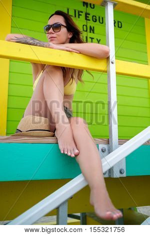 Beautiful woman in bikini sitting at the lifeguard station, Miami, USA.