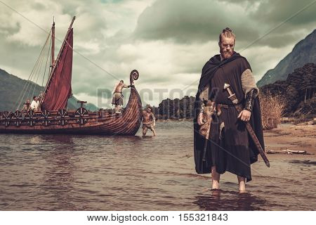 Viking warrior with sword standing near Drakkar on the seashore.