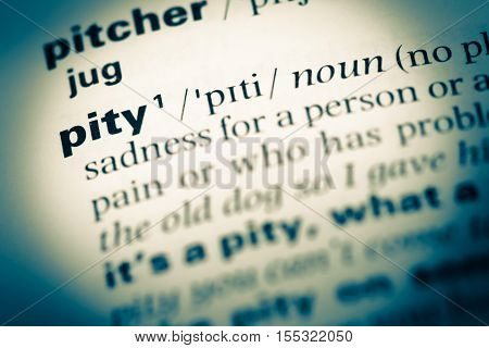 Close Up Of Old English Dictionary Page With Word Pity