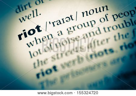 Close Up Of Old English Dictionary Page With Word Riot