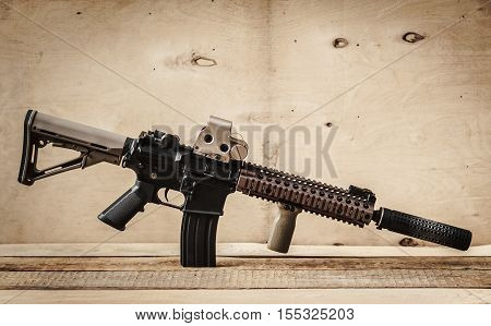 black assault rifle on a light wooden table