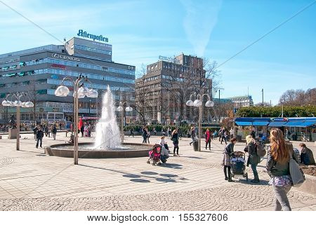 OSLO, NORWAY - APRIL 12, 2010: People near fountain on the Johanne Dybwad Square. The space named after the actress Johanne Dybwad (1867-1950)