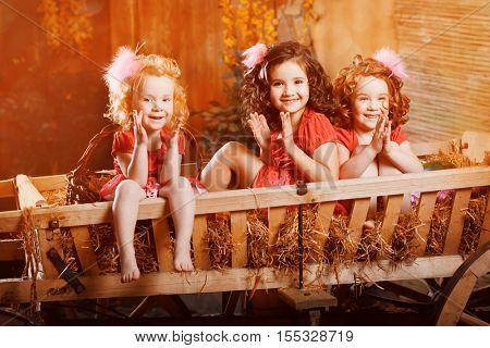 Three baby girls celebrate Halloween or Thanksgiving Day. Ð¡hildren preparing for the parade in the background decoration with pumpkins
