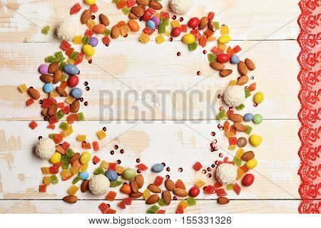 Mix of colorful dragee with raisins or peanuts inside marmalade or jelly candies almonds white chocolate coconut candies on vintage wooden background copy space