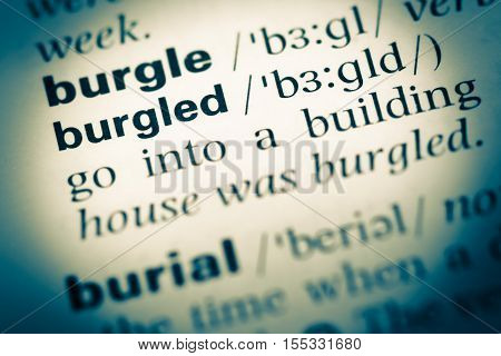Close Up Of Old English Dictionary Page With Word Burgled
