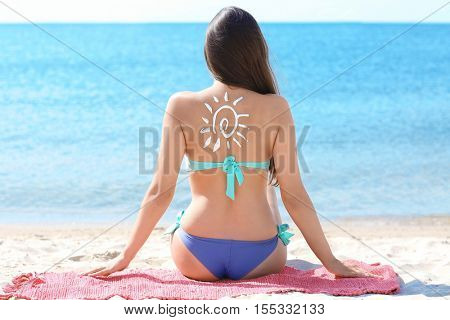 Woman with sun block cream on back at beach