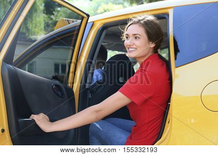 Beautiful young woman sitting on backseat in car with opened door