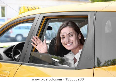 Beautiful young woman sitting on backseat in car