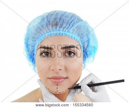 Plastic surgery concept. Hands in gloves marking women face