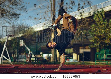 BBoy doing handstand on basketball court toned image