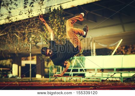 BBoy doing jump stunt on street toned image