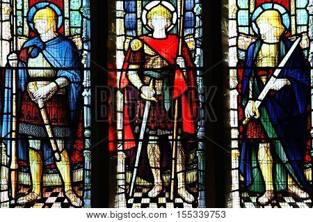 Carmarthen, Wales, UK, October 22, 2016 :  Medieval knight saints on a stained glass window at St Peter's Church in the city centre