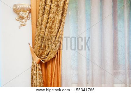 Part of beautifully draped curtain and wall with patterns.