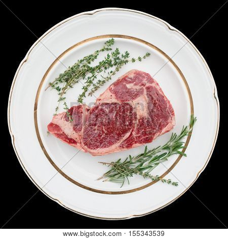 Raw rib-eye steak with aromatic herbs on plate, isolated on black
