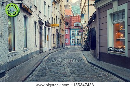 RIGA, LATVIA - MARCH, 03: Evening romantic street in old town of Riga in the end of this street there is an oldest restorant in Riga(since 1221).