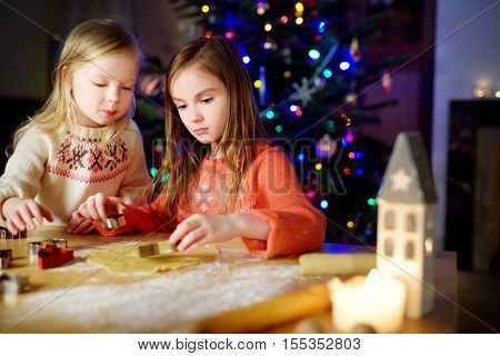 Two Adorable Little Sisters Baking Christmas Cookies By A Fireplace