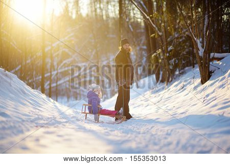 Young father and his daughter having fun with a sleight in beautiful winter park on sunset