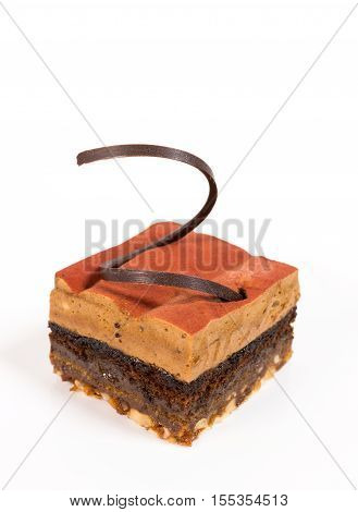 A square piece of chocolate pie with coffee mousse and chocolate curls on top
